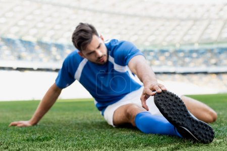 Photo for Selective focus of professional soccer player in blue and white uniform stretching on football pitch at stadium - Royalty Free Image