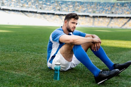 Photo for Professional soccer player in blue and white uniform sitting on football pitch with sports bottle at stadium - Royalty Free Image