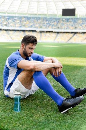Photo pour Footballeur professionnel en uniforme bleu et blanc assis sur un terrain de football avec bouteille de sport au stade - image libre de droit