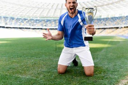 Photo pour Footballeur professionnel en uniforme bleu et blanc avec coupe de sport debout sur les genoux sur le terrain de football et criant au stade - image libre de droit