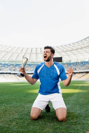 Photo for Professional soccer player in blue and white uniform with sports cup standing on knees on football pitch and shouting at stadium - Royalty Free Image