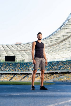 Photo for Handsome young sportsman on running track at stadium - Royalty Free Image