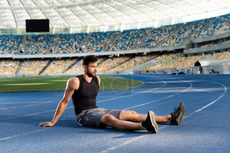 Photo for Handsome sportsman resting on running track at stadium - Royalty Free Image