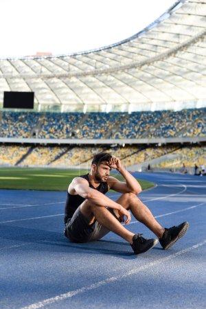 tired handsome sportsman resting on running track at stadium