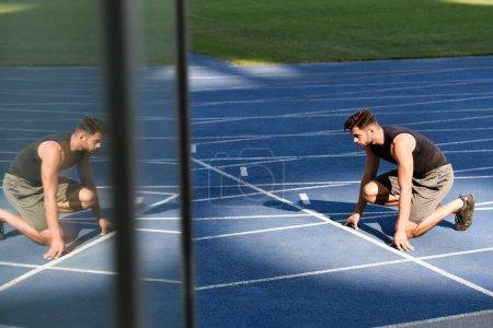 Photo pour Foyer sélectif du beau coureur en position de départ sur la piste de course au stade - image libre de droit