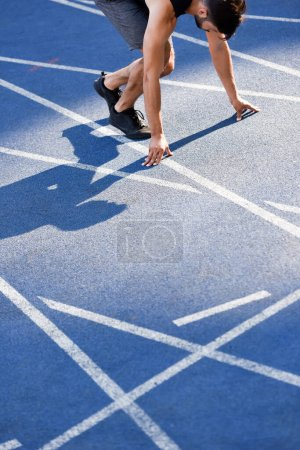 Photo for Cropped view of handsome runner in start position on running track at stadium - Royalty Free Image