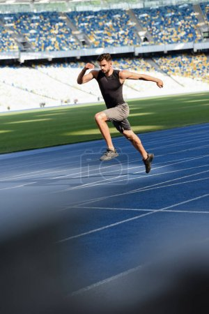 Photo pour Foyer sélectif du coureur beau rapide s'exerçant sur la piste de course au stade - image libre de droit