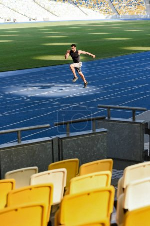 Photo for Selective focus of seats and fast handsome runner exercising on running track at stadium - Royalty Free Image