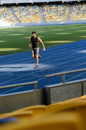 selective focus of fast handsome runner exercising on running track at stadium