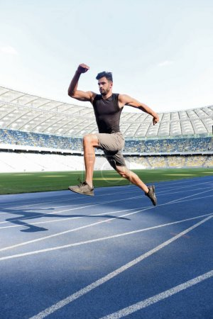 Photo for Handsome runner exercising on running track at stadium - Royalty Free Image