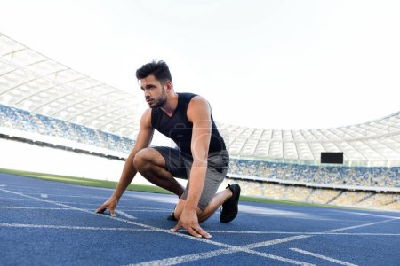 Photo for Handsome runner in start position on running track at stadium - Royalty Free Image