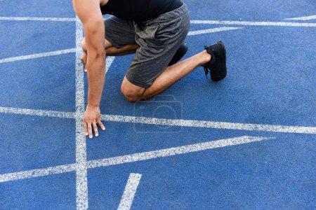Photo pour Vue recadrée du coureur en position de départ sur la piste de course au stade - image libre de droit