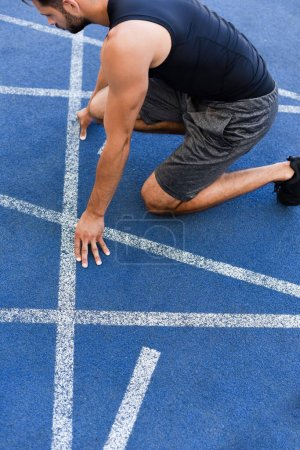 Photo for Cropped view of runner in start position on running track at stadium - Royalty Free Image