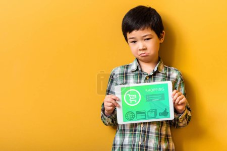 Photo for Upset asian boy holding digital tablet with shopping app on yellow - Royalty Free Image