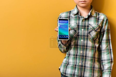 Photo for Sad asian boy holding smartphone with booking app on yellow - Royalty Free Image