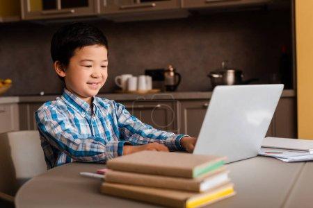 Photo pour Un garçon asiatique souriant étudie en ligne avec un ordinateur portable et des livres à la maison pendant la quarantaine - image libre de droit