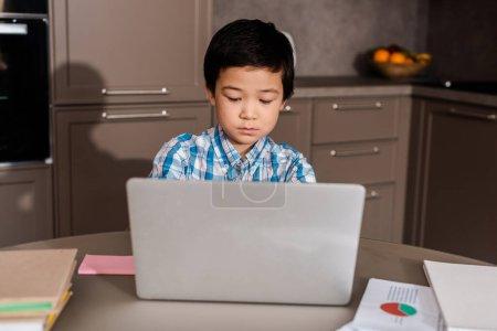 Photo pour Asian garçon étudiant en ligne avec un ordinateur portable à la maison pendant la quarantaine - image libre de droit