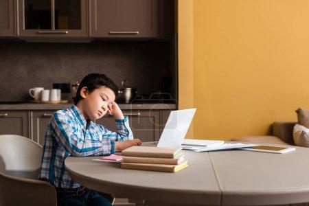 Photo pour Asian garçon étudiant en ligne avec des livres et un ordinateur portable à la maison pendant la quarantaine - image libre de droit