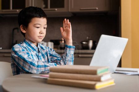 Photo pour Asian child with hand up studying online with laptop at home during self isolation - image libre de droit