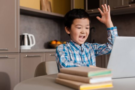 emotional asian boy with hand up shouting and studying online with laptop at home during self isolation