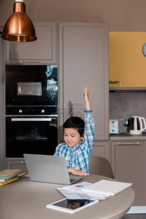 Photo pour Mignon garçon asiatique avec main up étudiant en ligne avec ordinateur portable à la maison pendant l'auto isolement - image libre de droit