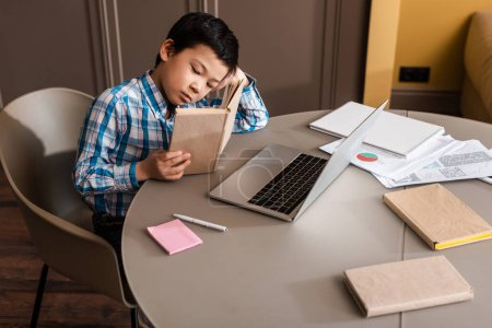 Photo pour Asian child reading book and studying online with laptop at home during self-isolation - image libre de droit