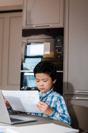 Photo for Asian boy studying online with papers and laptop at home during self isolation - Royalty Free Image