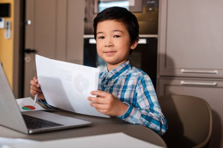 Photo for Happy asian boy studying online with papers and laptop at home during self isolation - Royalty Free Image
