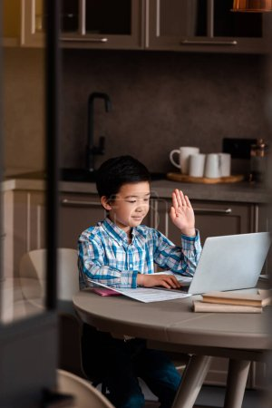 Photo pour Asian boy with hand up studying online with laptop at home during self isolation, selective focus - image libre de droit