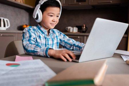 Photo pour Un garçon asiatique souriant étudiant en ligne avec des livres, un ordinateur portable et des écouteurs à la maison pendant la quarantaine - image libre de droit
