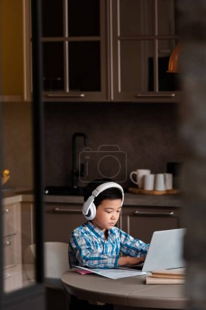 Photo for Asian boy studying online with books, laptop and headphones at home during quarantine - Royalty Free Image