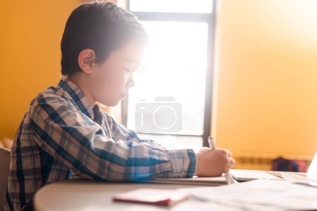 Photo for Asian boy writing and studying at home with sunlight during quarantine - Royalty Free Image