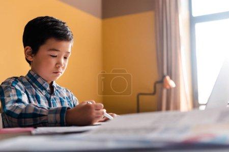Photo pour Asian garçon écrivant et étudiant en ligne avec un ordinateur portable à la maison pendant la quarantaine - image libre de droit