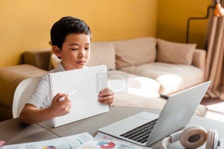 Photo pour Asian garçon étudiant en ligne avec bloc-notes et ordinateur portable à la maison pendant l'isolement - image libre de droit