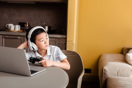 Photo for KYIV, UKRAINE - APRIL 22, 2020: bored asian boy playing video game with joystick and laptop on quarantine - Royalty Free Image