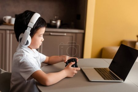 Photo for KYIV, UKRAINE - APRIL 22, 2020: asian boy playing video game with joystick and laptop with blank screen on quarantine - Royalty Free Image