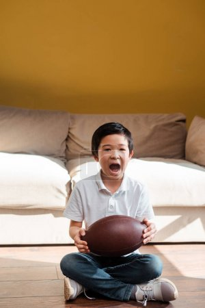 excited asian boy with rugby ball yelling and watching sports match at home on quarantine