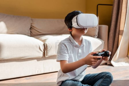 KYIV, UKRAINE - APRIL 22, 2020: boy playing video game with joystick and virtual reality headset on self isolation