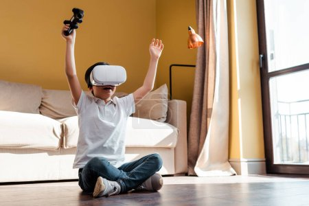 Photo for KYIV, UKRAINE - APRIL 22, 2020: excited boy playing video game with joystick and virtual reality headset on self isolation - Royalty Free Image