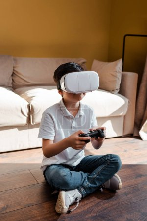 KYIV, UKRAINE - APRIL 22, 2020: child playing video game with joystick and virtual reality headset on self isolation