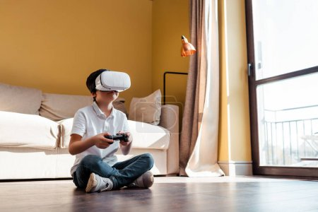KYIV, UKRAINE - APRIL 22, 2020: kid playing video game with joystick and virtual reality headset on self isolation