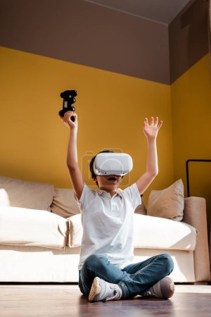 KYIV, UKRAINE - APRIL 22, 2020: cheerful boy playing video game with joystick and virtual reality headset on self isolation