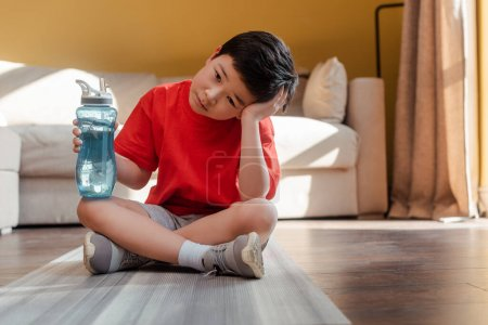 Photo for Bored sportive asian boy with sports bottle sitting on fitness mat at home during quarantine - Royalty Free Image