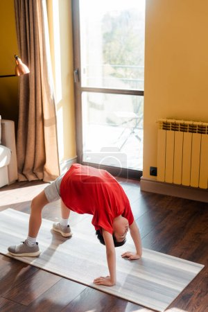 sportive asian boy in bridge pose on fitness mat at home during quarantine