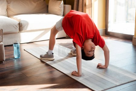 athletic asian boy in bridge pose on fitness mat at home during quarantine
