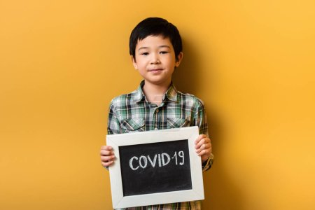 smiling asian boy holding board with covid-19 sign on yellow during quarantine