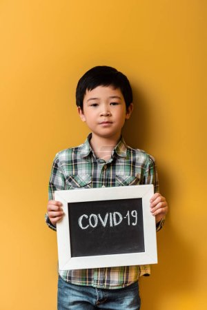 asian boy holding board with covid-19 sign on yellow during quarantine