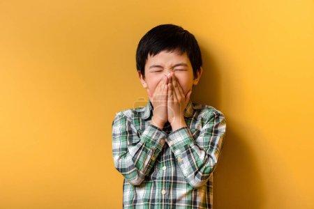 Photo for Sick asian boy sneezing on yellow during quarantine - Royalty Free Image