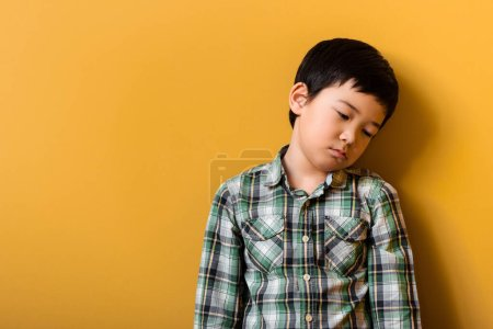 Photo for Sad adorable asian boy standing on yellow - Royalty Free Image