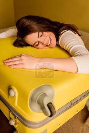 cheerful young woman lying on luggage, end of quarantine concept